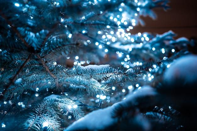Рождественская елка с шишками на городской улице освещается с гирляндой. Бесплатные Фотографии