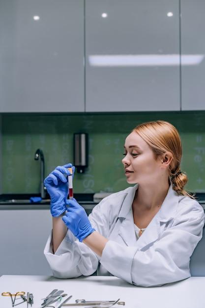 実験室で試験管を見ている女性の医学または科学研究者。 無料写真