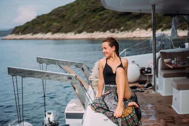 ヨットの上でビキニ水着に座っていると太陽を浴びて若いスリムな女性 無料写真