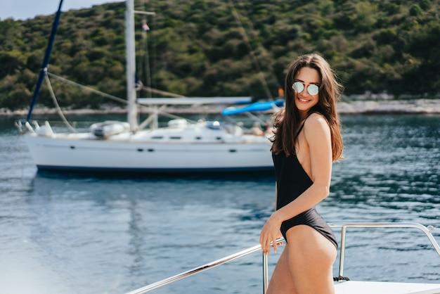 Молодая стройная женщина, сидящая в купальном костюме бикини на яхте в солнечных очках и греющаяся на солнце Бесплатные Фотографии