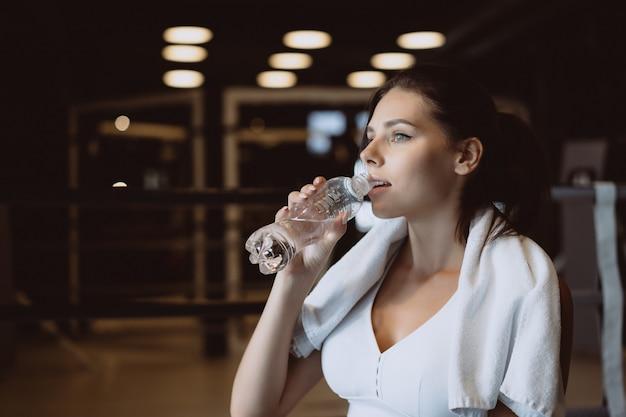 Шикарная молодая женщина с полотенцем на плечах пьет воду из бутылки в спортзале Бесплатные Фотографии