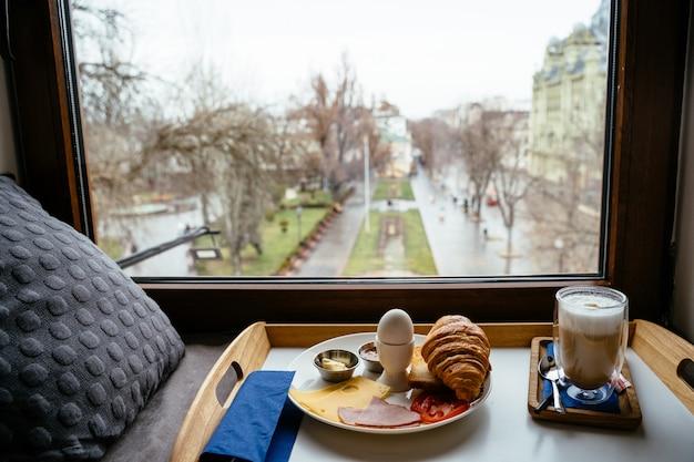 窓際の木製テーブルで朝食します。 無料写真