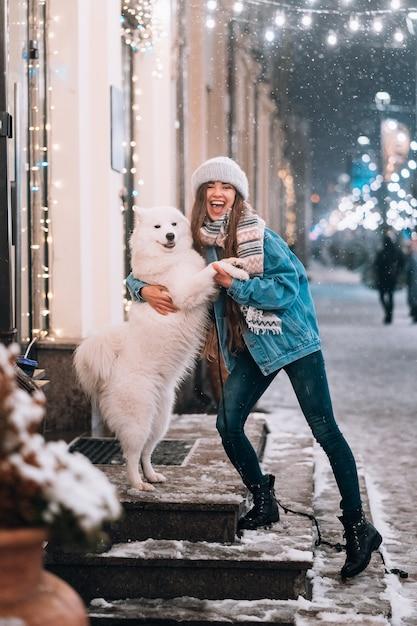 女性は夜の街で彼女の犬を抱いています。 無料写真