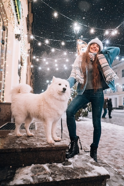 白い犬と一緒に歩いている女性 無料写真