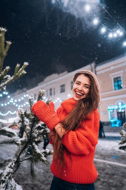 Молодая женщина позирует возле елки на улице Бесплатные Фотографии
