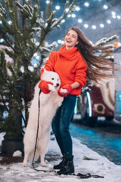 Женщина обнимает свою собаку на ночной улице Бесплатные Фотографии