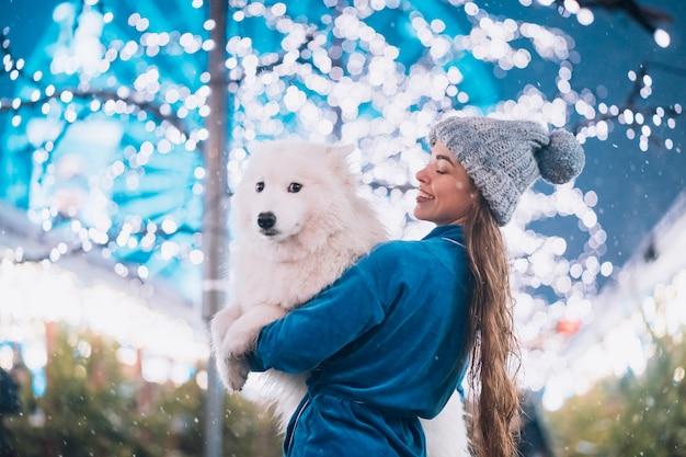 Женщина несет свою собаку на руках Бесплатные Фотографии