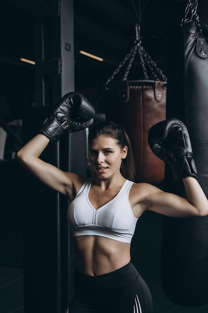 ボクシング女性がサンドバッグでポーズします。強くて独立した女性の概念 無料写真