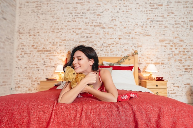 Довольно счастливая женщина на кровати у себя дома Бесплатные Фотографии