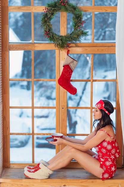 窓際の家に座っている赤いパジャマを着て美しい若いブルネットの女性 無料写真