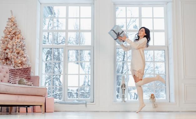 Красивая молодая женщина в белом платье позирует с подарочной коробке Бесплатные Фотографии