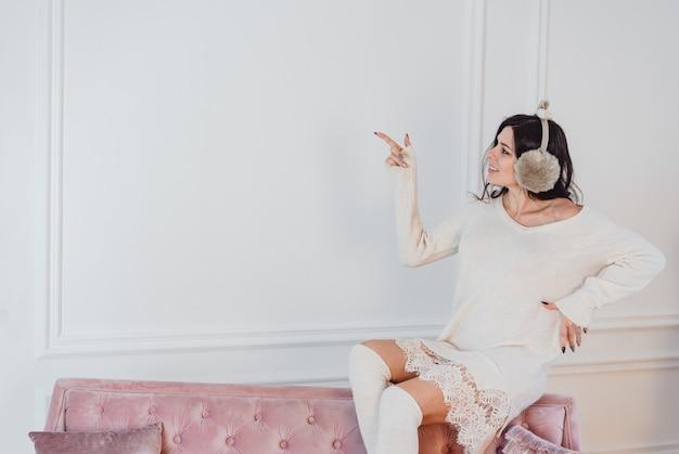 部屋でポーズをとって白いドレスの若い女性 無料写真
