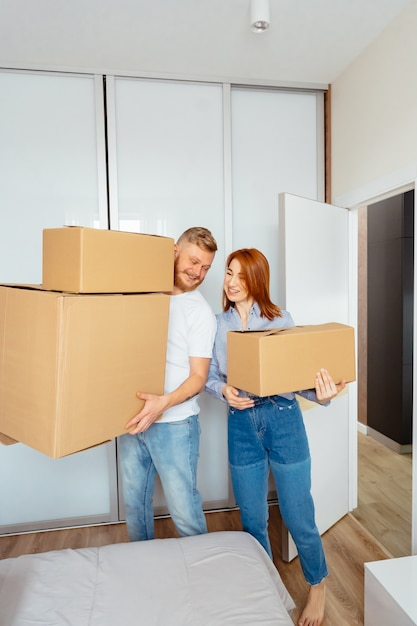Счастливая пара держит картонные коробки и переезжает на новое место Бесплатные Фотографии