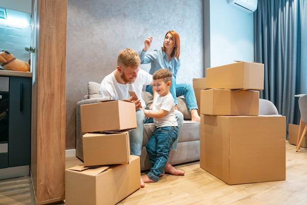 Молодая счастливая семья с ребенком, распаковка коробок вместе сидя на диване Бесплатные Фотографии