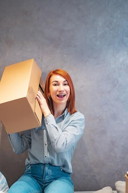 Молодая женщина держит картонные коробки и трясет его Бесплатные Фотографии