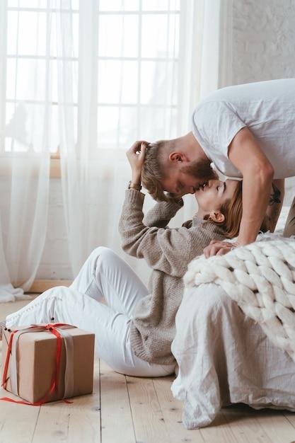 ベッドの上の男は床に座っている女性にキスします 無料写真