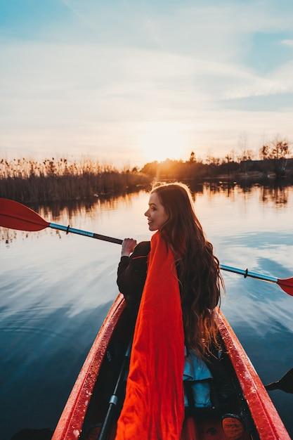Счастливая милая женщина держа весло в каяке на реке Бесплатные Фотографии