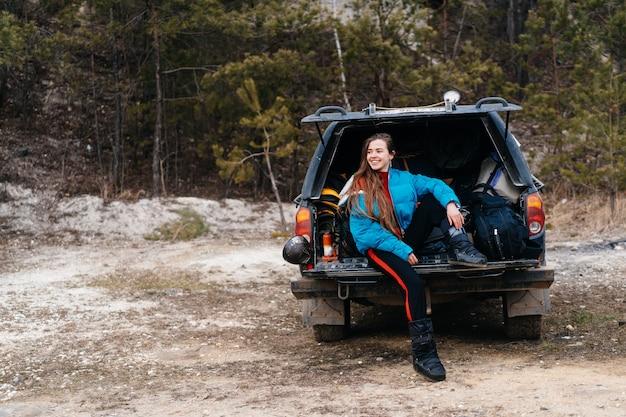 車のトランクに座って自然を楽しむ若い女性 無料写真