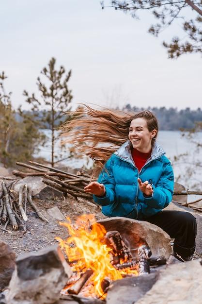 たき火の隣に座って幸せな若いブルネットの女性 無料写真