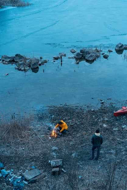 湖の男が火を起こす 無料写真