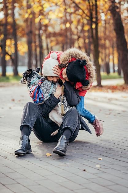Счастливая мать и ее дочь, играя с собакой в осенний парк Бесплатные Фотографии