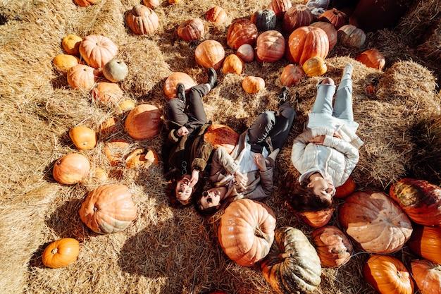 Молодые девушки лежат на стогах сена среди тыкв Бесплатные Фотографии