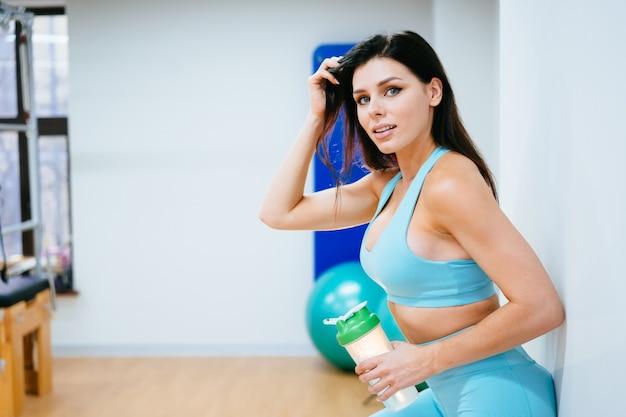 Спортсменка отдыхает и пьет воду на лестнице в тренажерном зале Бесплатные Фотографии