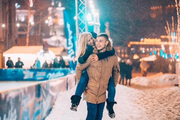 Веселая и игривая пара в теплых зимних нарядах дурачится Бесплатные Фотографии