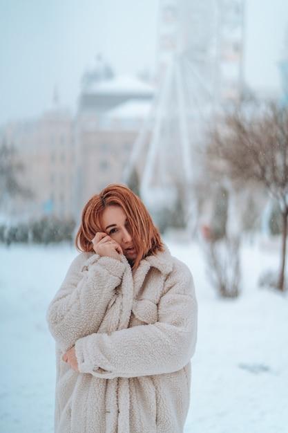 雪の降る寒い冬の日の外の女性 無料写真