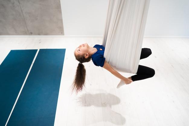 Портрет красивая молодая девушка занимается мухой йоги на холстах. Бесплатные Фотографии