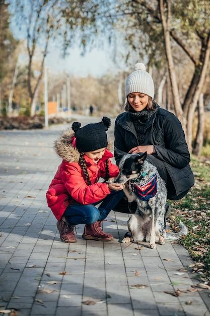 幸せな母と娘の秋の公園で犬と遊ぶ 無料写真