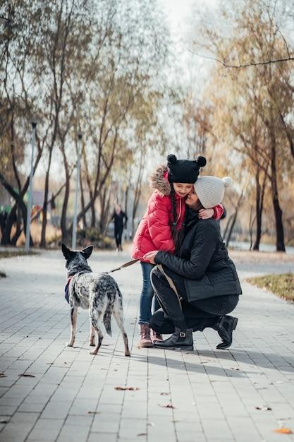 Счастливая мать и ее дочь гуляют с собакой в осеннем парке Бесплатные Фотографии