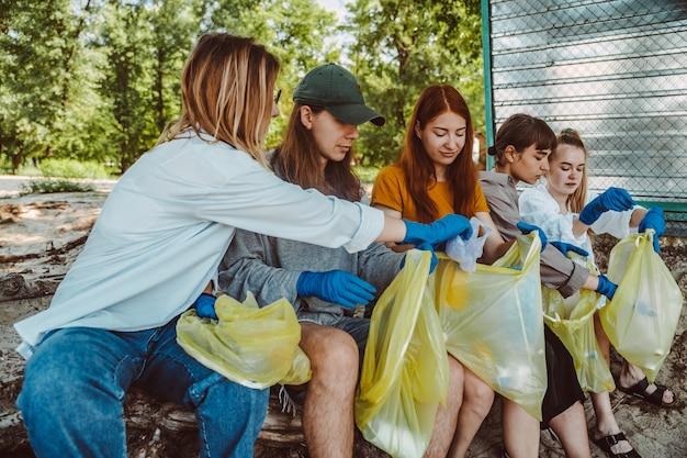 公園でプラスチック廃棄物を収集する活動家の友人のグループ。環境保全。 無料写真