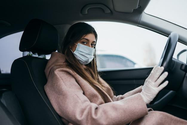 Молодая женщина в маске и перчатки за рулем автомобиля. Бесплатные Фотографии