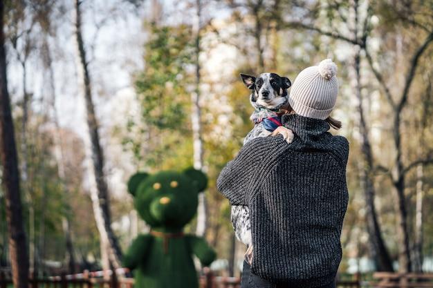 女の子が雑種犬を腕に抱えています。動物の世話をする。 無料写真