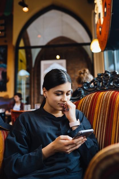 Хорошенькая молодая девушка отдыхает на большом мягком стуле в кафе, болтает по телефону Бесплатные Фотографии