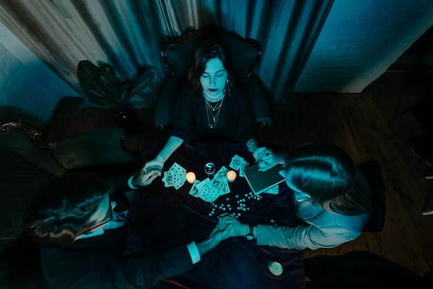人々はキャンドルでテーブルで夜の手を握る 無料写真