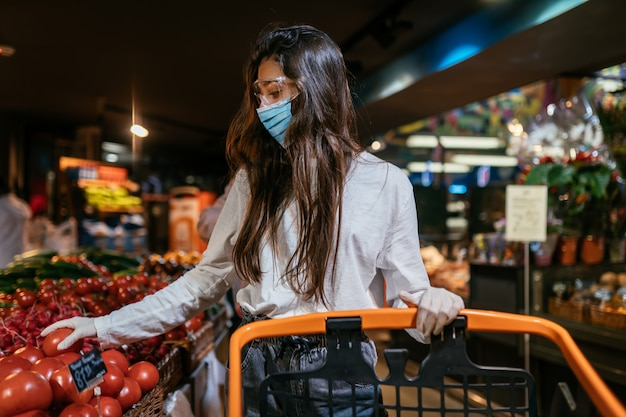 Женщина с хирургической маской собирается купить помидоры. Бесплатные Фотографии