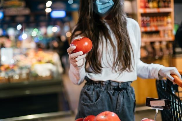 サージカルマスクを持つ女性はトマトを購入する予定です。 無料写真