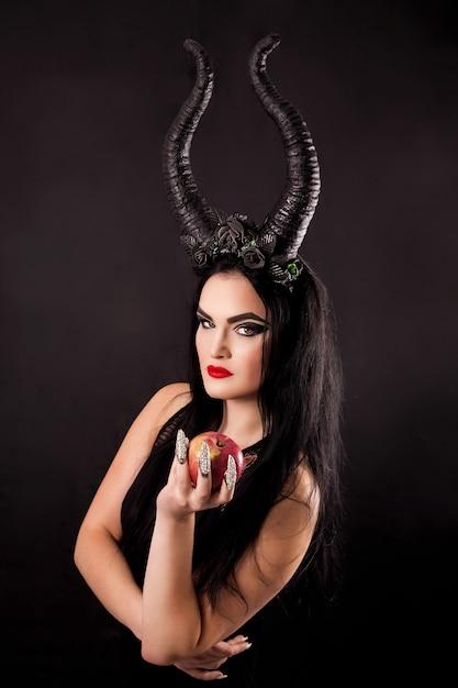 角のある魔女の手の中のリンゴ Premium写真