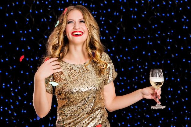 黒の背景上のシャンパングラスで黄金のドレスで美しい女性 Premium写真
