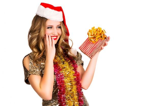 Красивая девушка в новогодней шапке с подарком на белом фоне Premium Фотографии