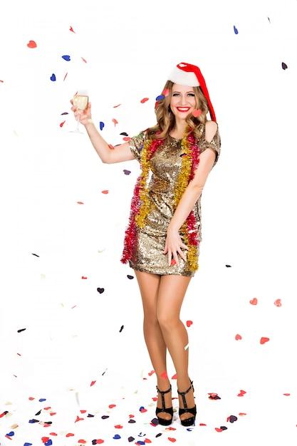 Счастливая молодая женщина в вечернем платье празднует на белом фоне Premium Фотографии