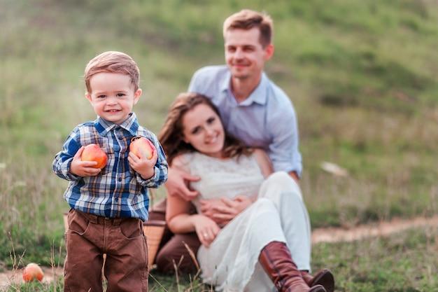 ピクニックで幸せな家族。フォアグラウンドでリンゴと小さな男の子 Premium写真