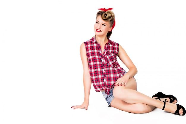 ショートパンツと白い背景の上の床に座ってハイヒールでセクシーなピンナップガール Premium写真