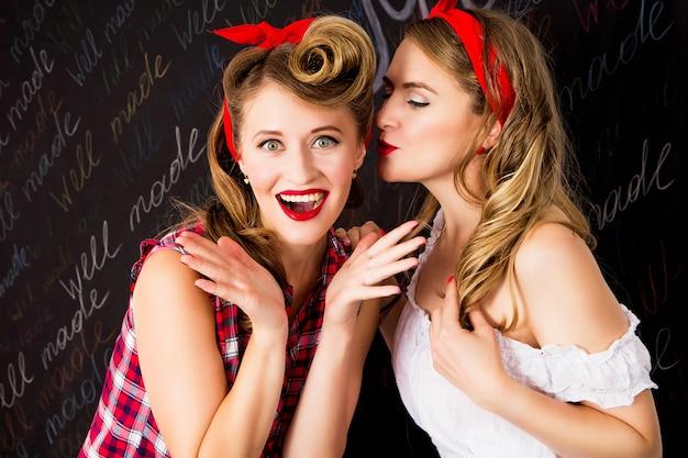 Красивые женщины разговаривают. девушки в стиле пин ап с идеальной прической и макияжем Premium Фотографии