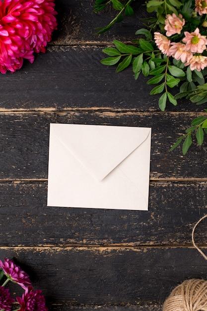 暗いビンテージテーブルの上の美しい花と封筒 Premium写真