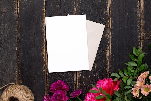 暗いビンテージテーブルの上の美しい花と白いギフトカード Premium写真