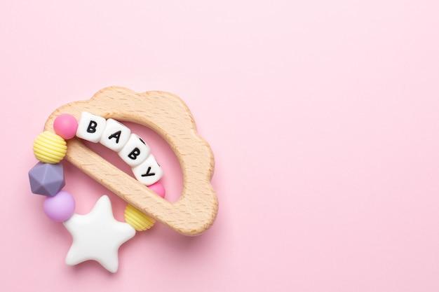 ピンクの赤ちゃん木のおもちゃと歯が生えるパステルカラー Premium写真