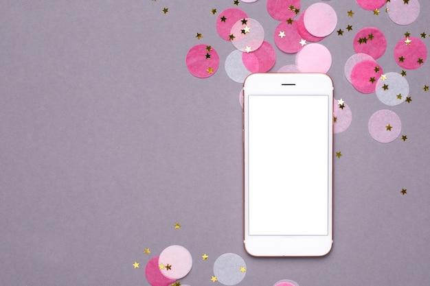 携帯電話のモックアップと灰色の金の星とピンクの紙吹雪 Premium写真